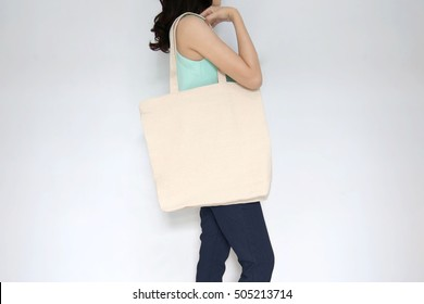 Mock-up. Girl is holding blank canvas tote bag. Handmade eco shopping bag for girls.