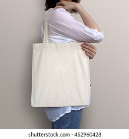 Mock-up. Girl is holding blank cotton tote bag.
