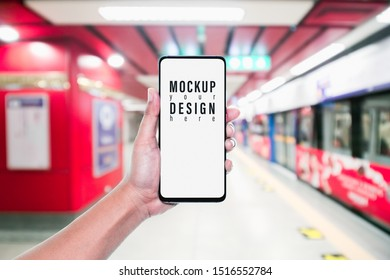 Mockup of hand using mobile phone with copy space blank screen for your advertisement with blurred view of red subway, internet social media technology advertisement marketing concept.
