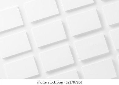 Mockup of horizontal business cards stacks arranged in rows at white textured paper background.