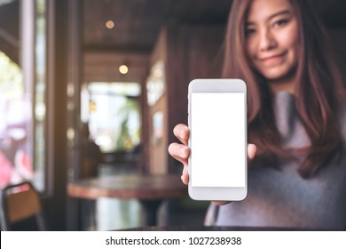 Mockup image of a beautiful asian woman holding and showing white mobile phone with blank desktop screen in cafe