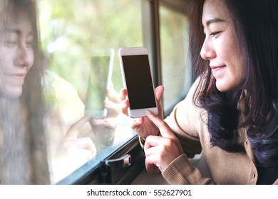 Mockup image of a beautiful asian woman using on the smart phone with blank black screen in the room , feeling happy and smiley face and  reflections in glass