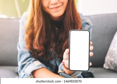 Mockup image of a beautiful woman holding and showing black mobile phone with blank screen in cafe
