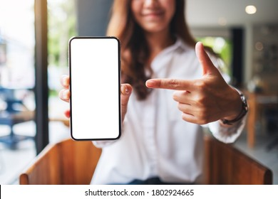 Mockup image of a beautiful woman pointing finger at a mobile phone with blank white screen  - Shutterstock ID 1802924665