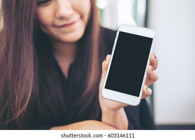 Mockup image of a beautiful woman with smiley face holding and showing white mobile phone with blank black screen  in modern cafe