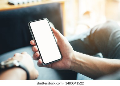 Mockup image blank screen cell phone.men hand holding texting using mobile on sofa at home office.white empty space for advertise text. contact business,people communication,technology device concept