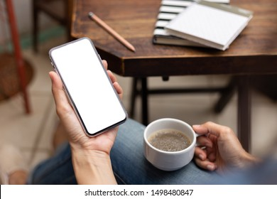 Mockup image blank white screen cell phone.men hand holding texting using mobile on desk at home office. background empty space for advertise text. contact business,people communication,technology