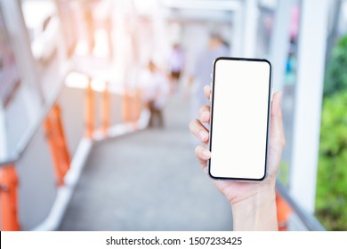 Mockup image blank white screen cell phone.men hand holding texting using mobile at subway station. background empty space for advertise text. contact business,people communication,technology