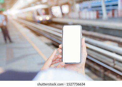 Mockup image blank white screen cell phone.men hand holding texting using mobile at subway station in urban. background empty space for advertise text.people contact marketing business and technology