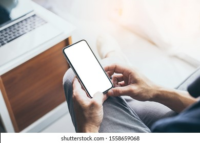 Mockup image blank white screen cell phone.men hand holding texting using mobile on desk at home office. background empty space for advertise text.people contact marketing business and technology