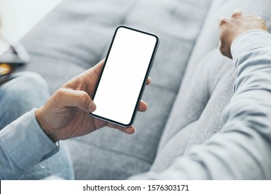 Mockup image blank white screen cell phone.men hand holding texting using mobile on sofa at home office. background empty space for advertise text.people contact marketing business and technology
