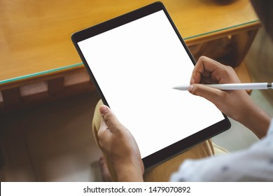 Mockup image of business woman hand holding black tablet computer pc  with blank white screen and using pencil for writing or drawing on it. Top view.