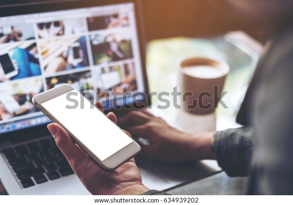 Mockup image of a business woman holding mobile phone with blank white screen while using laptop with coffee cup on the table in office