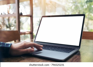Mockup image of business woman using and touching on laptop with blank white desktop screen on wooden table in cafe