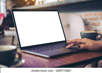 Mockup image of a businesswoman using laptop with blank white desktop screen with coffee cup on wooden table in cafe