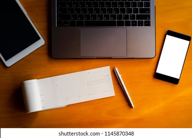 Mockup image of cheque book, pen, digital tablet, laptop computer and mobile smart phone with blank white screen on the wooden desk background. Top view. clipping path.