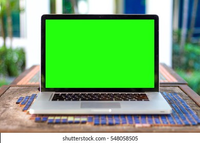 Mockup image of green screen display laptop computer,cup and diary on wood table at coffee shop background for business