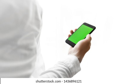 Mockup image of hand holding black mobile phone with green screen