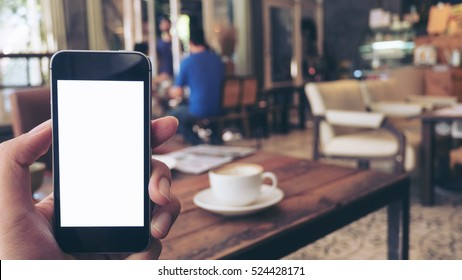 Mockup image of hand holding black mobile phone with blank white screen and hot latte coffee on vintage wood table in cafe