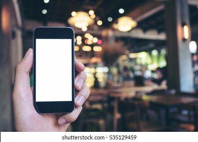 Mockup image of hand holding black mobile phone with blank white screen in cafe