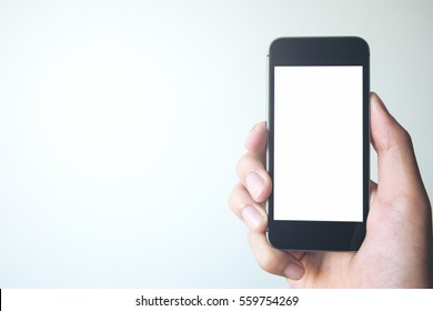 3838aa991e93f Mockup image of hand holding black mobile phone with blank white screen on  white background room
