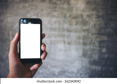 Mockup image of hand holding black mobile phone with blank white screen on concrete polishing wall background