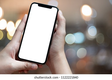 Mockup image of hand holding mobile phone with blank white Full screen in cafe