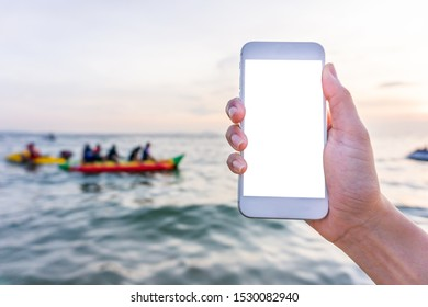 Mockup image of a hand holding and showing white mobile phone with blank desktop screen in front of blur the sea sky and person play banana boat background