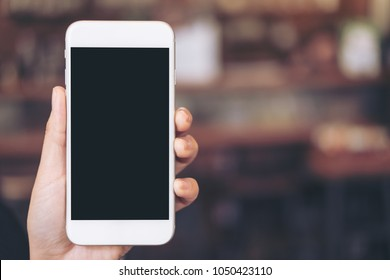 Mockup image of a hand holding white mobile phone with blank black desktop screen with blur background