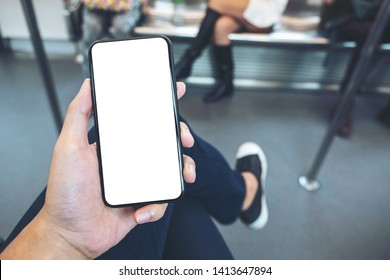 Mockup image of hand holding white mobile phone with blank black screen in subway with many people in background