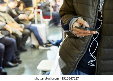 Mockup image of hand holding white mobile phone with blank black screen in subway with many people in background, copy space for text