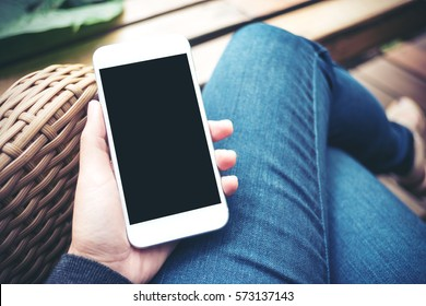 Mockup image of hand holding white mobile phone with blank black screen on thigh