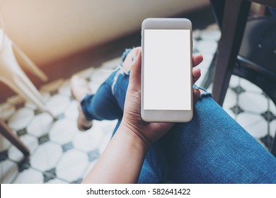 Mockup image of hand holding white mobile phone with blank white screen on thigh with a vintage tile floor in cafe , feeling relaxed