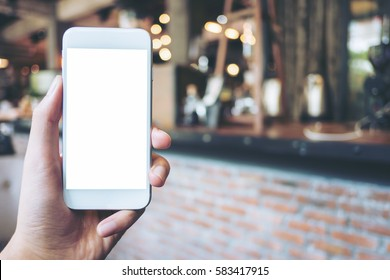 Mockup image of a hand holding white mobile phone with blank white screen in vintage cafe