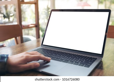 Mockup image of a hand using and touching laptop with blank white desktop screen on wooden table in cafe