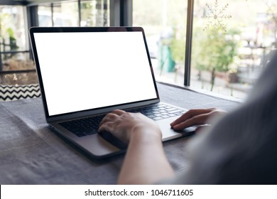 Mockup image of a hand using and touching laptop with blank white desktop screen on table in cafe