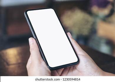Mockup image of hands holding black mobile phone with blank white screen in vintage cafe