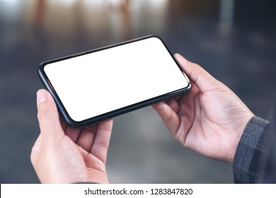 Mockup image of hands holding black mobile phone with blank white screen  horizontally