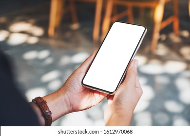Mockup image of hands holding black mobile phone with blank desktop screen