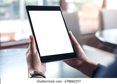 Mockup image of hands holding black tablet pc with white blank screen in modern cafe