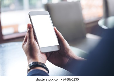 Mockup image of hands holding mobile phone with blank white screen in vintage cafe