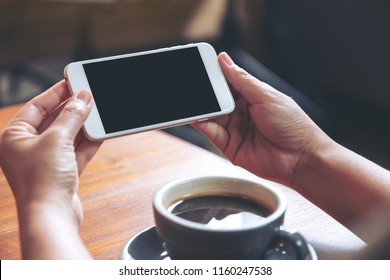 Mockup image of hands holding and using a white mobile phone with blank black screen horizontally for watching with coffee cup on wooden table