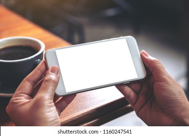 Mockup image of hands holding and using a white mobile phone with blank screen horizontally for watching with coffee cup on wooden table