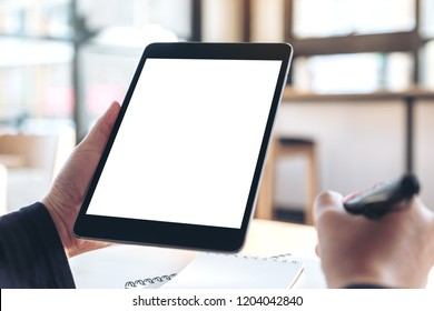 Mockup image of hands holding and using black tablet pc with blank white desktop screen while writing on notebooks in office