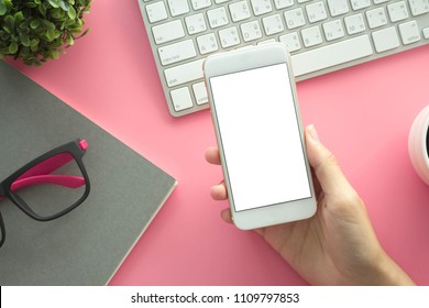 Mockup image of hands holding white mobile phone with blank white screen with Modern pink office desk with laptop and other supplies for input the text on copy space Top view, flat lay.