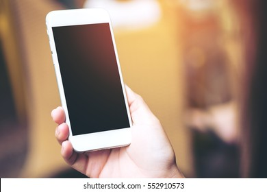 Mockup image of hands holding white mobile phone with blank white screen on vintage wooden room
