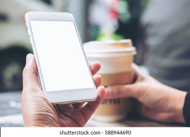Mockup image of hands holding white mobile phone with blank white screen and hot coffee cup in modern cafe