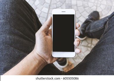 mockup image of hands holding white mobile phone with blank black screen, soft-focus in the background. over light and film colors tone