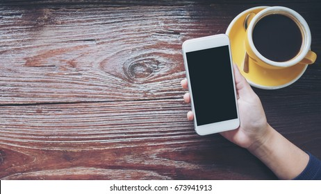 Mockup image of hands holding white mobile phone with blank black screen with yellow   hot coffee cups on vintage wooden table in restaurant