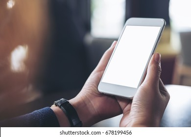 Mockup image of hands holding white mobile phone with blank white screen on table in cafe